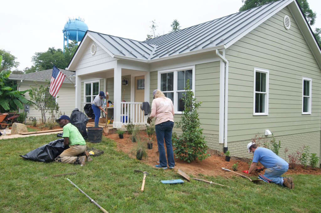 Volunteers and staff landscape the home
