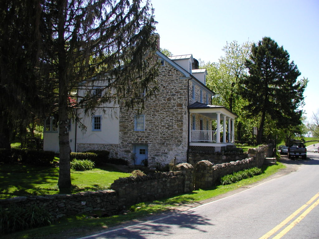 An old stone building with a stone wall next to a road.