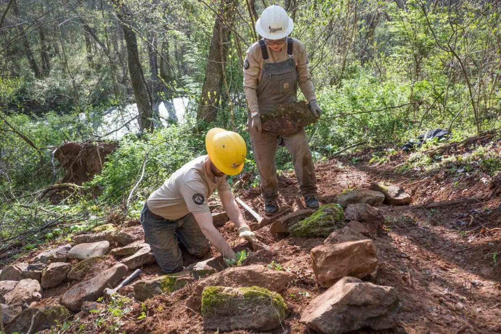 corps members place river stones