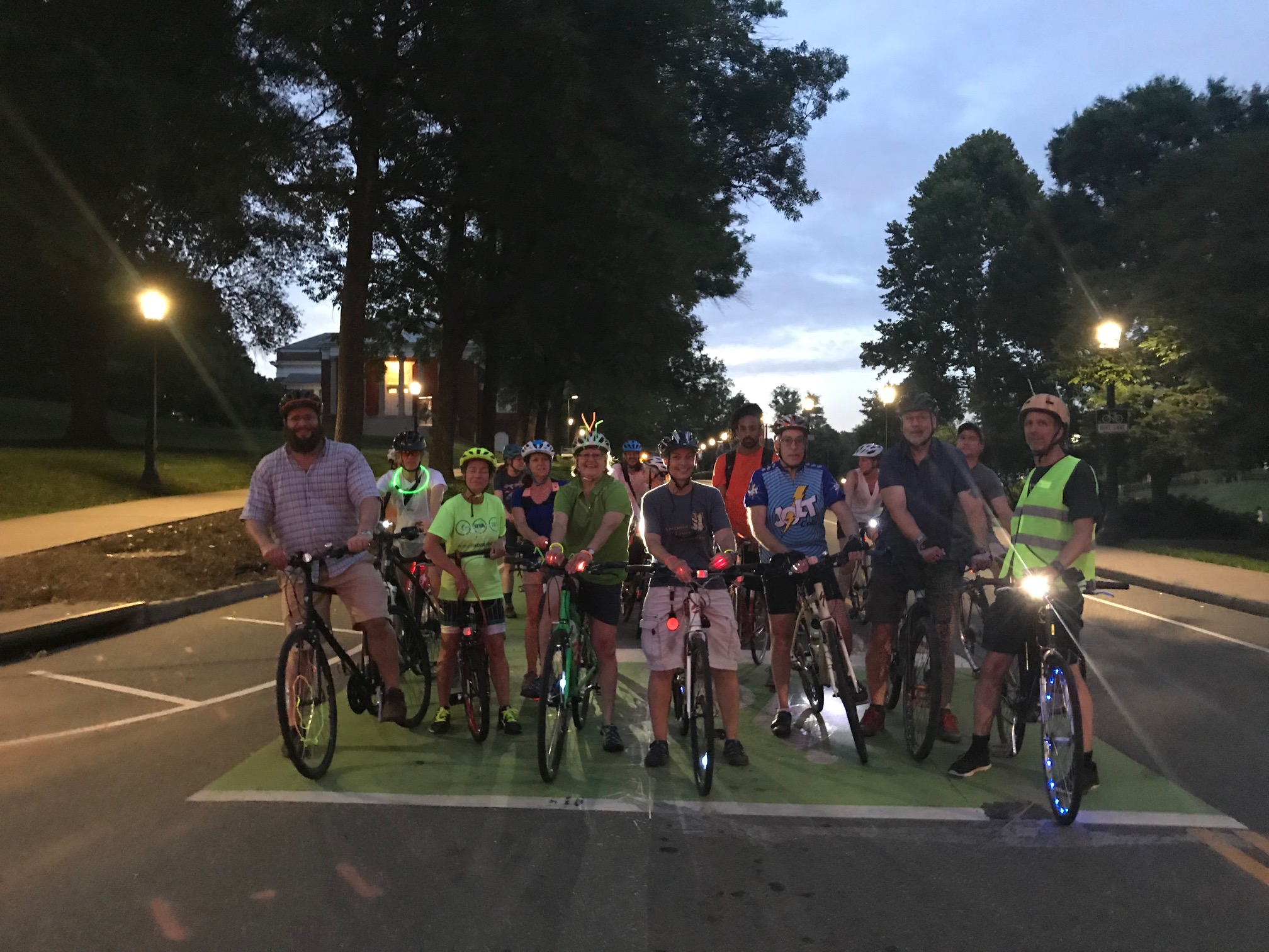 a group of people with their bikes, with lights and reflective gear at night