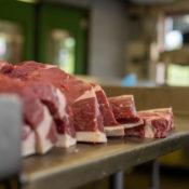 Freshly butchered steaks on a metal table.