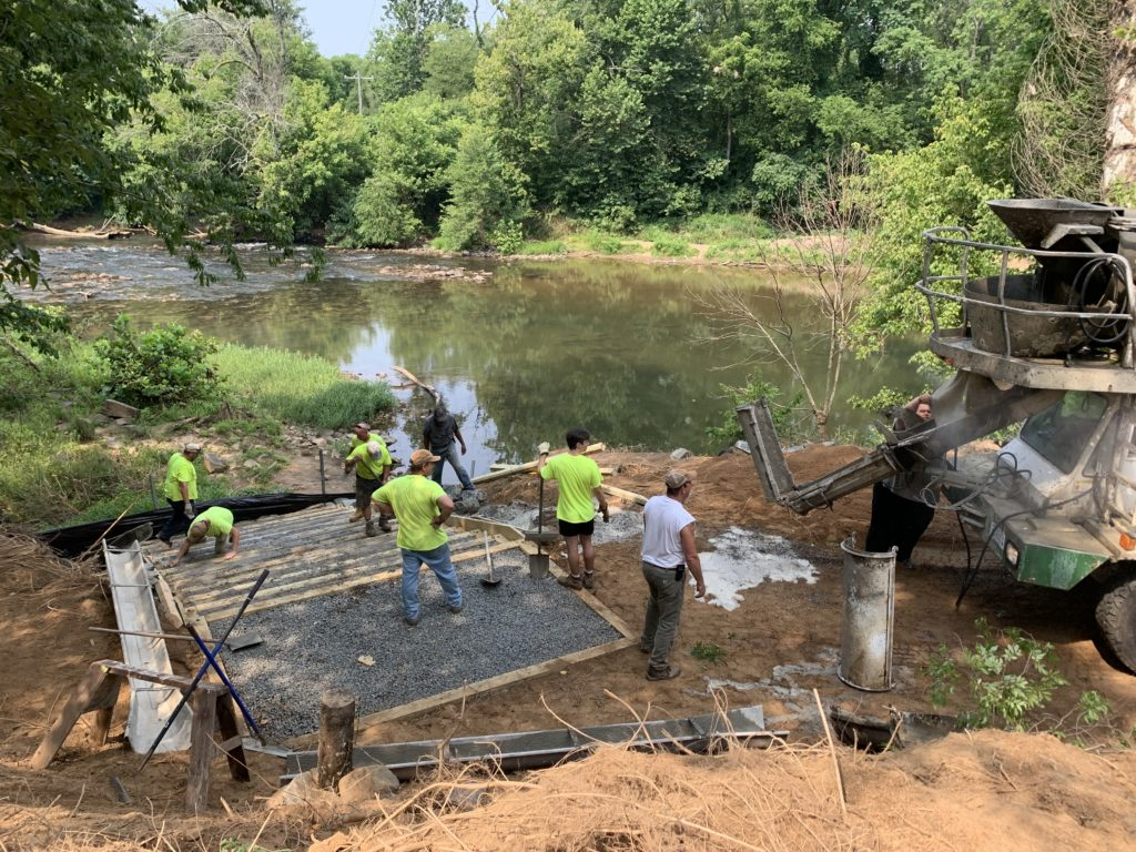 volunteers help lay cement and gravel at the boat launch