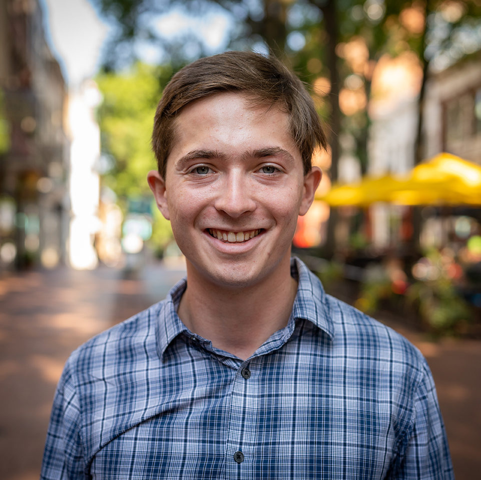 a young white man with a blurry background on downtown Charlottesville