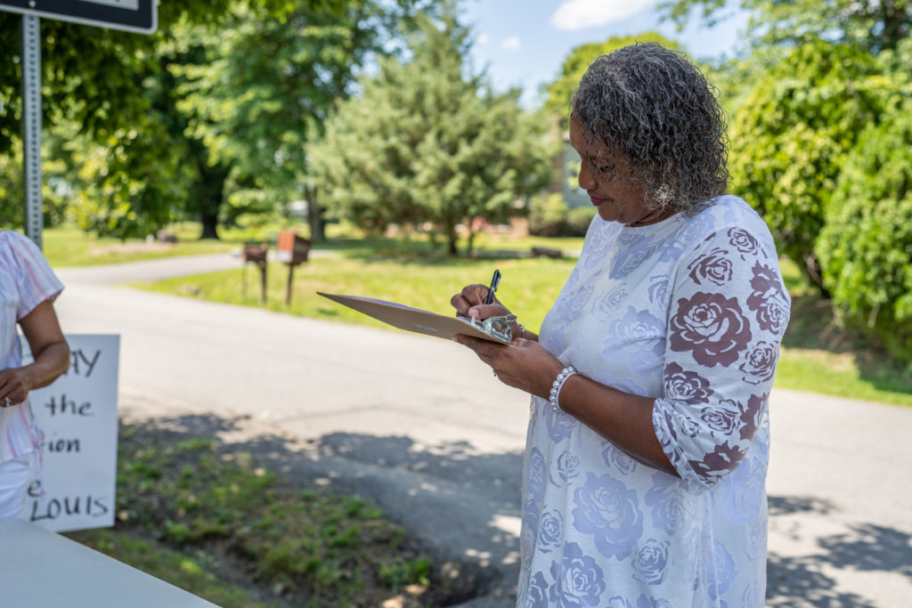 a Black woman signs a petition in St. Louis