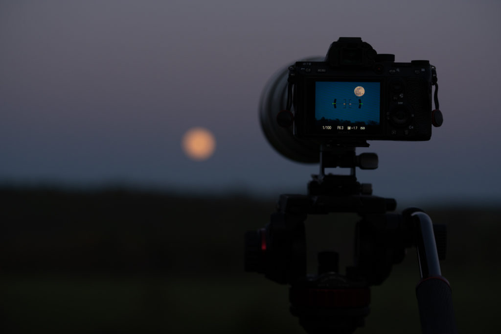 Camera screen showing moon in background.