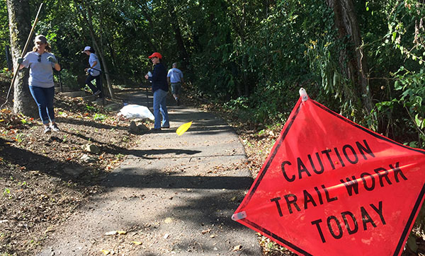 Image of volunteers working on forested trail with a red sign that says, ''Caution trail work today.''