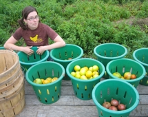 A woman stands next to buckets for harvesting produce.
